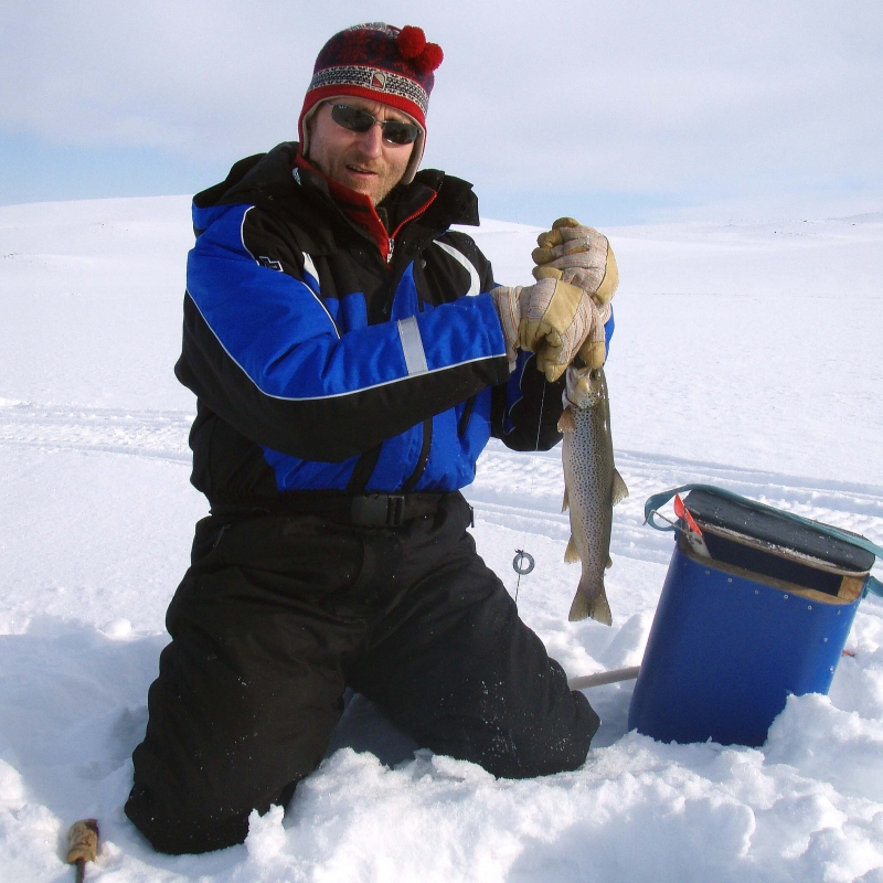 Ice fishing trip at a fell lake
